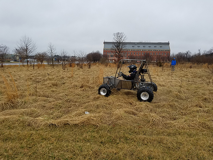 Baja vehicle being test driven on bumpy field near Exploration Hall at GW's VSTC campus