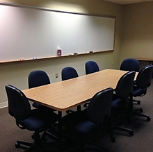 Conference room light wood table with 8 blue chairs and large whiteboard on the back wall