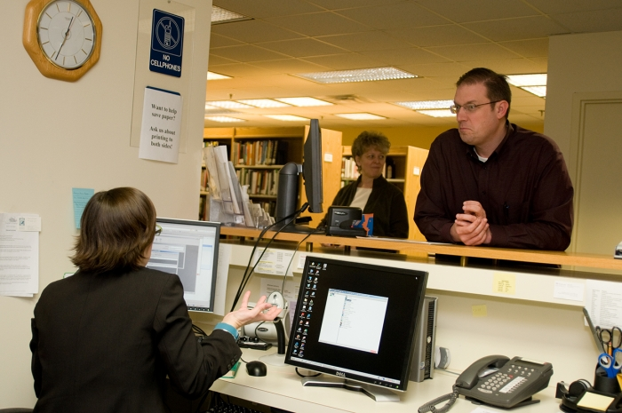 library staff talks to patrons at desk