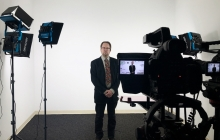 John Warren in a suit in the new film studio with camera and special lighting