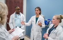 4 nursing faculty members talk in white coats