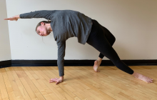 Woman in sideways full body yoga pose in exercise clothing