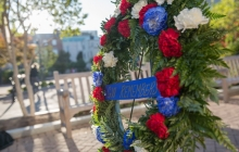 Memorial Day weath with red, blue, white flowers and words GW Remembers and a bench in the background