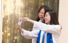 2 Female Nursing students take selfie at pinning ceremony